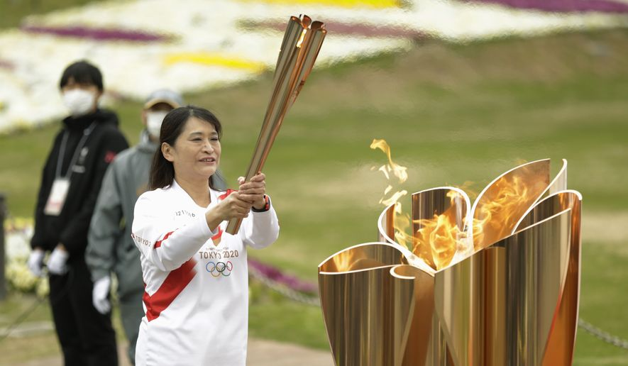 The last Olympic torch relay runner for the Osaka leg concludes the event in Suita, north of Osaka, western Japan, Wednesday, April 14, 2021. (AP Photo/Hiro Komae)