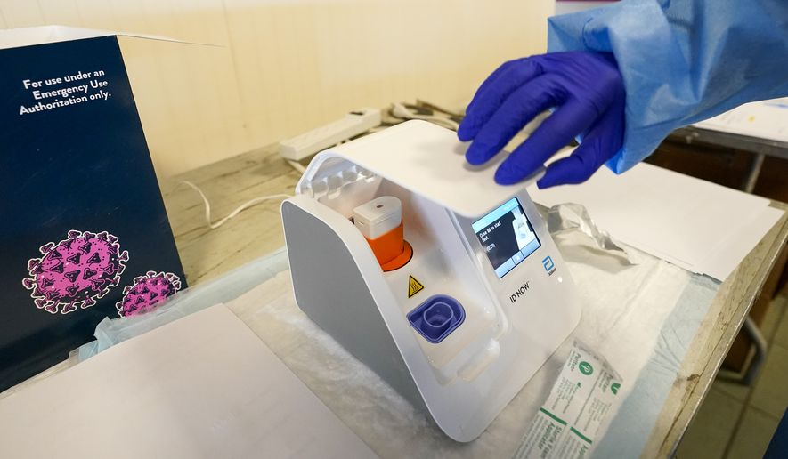 A Northwell Health lab technician uses the Abbott ID NOW COVID-19 rapid tester on a participant before a news conference, Wednesday, April 14, 2021 at a pop up COVID-19 vaccination sight at Belmont Park in Elmont , N.Y. (AP Photo/Mary Altaffer, Pool)