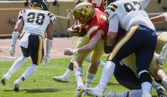 VMI quarterback Seth Morgan (4) crosses the goal line after a two-yard run with East Tennessee State's Max Evans (93) on his back for the first score of the game during the first half of an NCAA college football game Saturday, April 3, 2021, in Lexington, Va. (David Hungate/The Roanoke Times via AP)