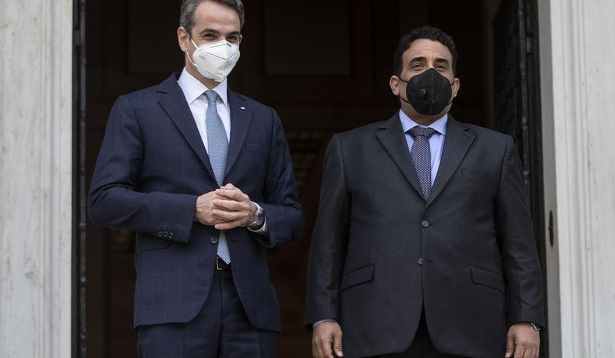 Greek Prime Minister Kyriakos Mitsotakis, left, and the head of the Presidential Council of Libya Mohamed al-Menfi, wear face masks to curb the spread of COVID-19 as they pose for photographers before their meeting, in Athens, on Wednesday, April 14, 2021.(AP Photo/Petros Giannakouris)