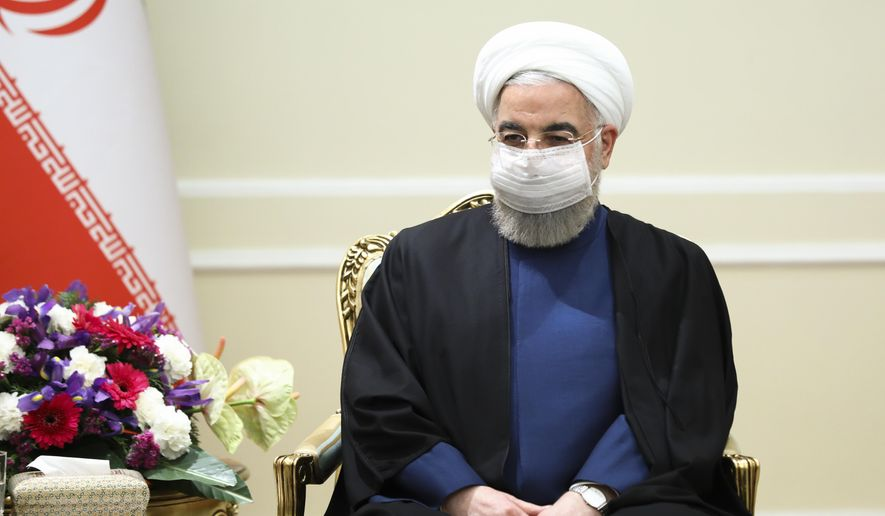 In this photo released by Russian Foreign Ministry Press Service, Iranian President Hassan Rouhani, wearing a face mask to curb the spread of COVD-19, listens to Russian Foreign Minister Sergey Lavrov during their talks in Tehran, Iran, Tuesday, April 13, 2021. (Russian Foreign Ministry Press Service via AP)