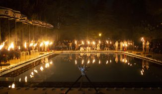 Israeli scouts light torches during a Memorial Day ceremony commemorating fallen soldiers, at the military cemetery at Mount Herzl in Jerusalem, Tuesday, April 13, 2021. (AP Photo/Maya Alleruzzo)