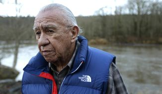 FILE - In this Jan. 13, 2014, file photo, Billy Frank Jr. poses for a photo near Frank's Landing on the Nisqually River in Nisqually, Wash. Gov. Jay Inslee on Wednesday, April 14, 2021, signed a measure that starts the process of honoring the late Frank, a Nisqually tribal member who championed treaty rights and protecting the environment, with a statue at the U.S. Capitol. (AP Photo/Ted S. Warren, File)