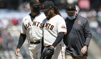 San Francisco Giants starting pitcher Johnny Cueto, middle, walks toward the dugout next to manager Gabe Kapler, left, as he leaves the game during the sixth inning of a baseball game against the Cincinnati Reds in San Francisco, Wednesday, April 14, 2021. (AP Photo/Jeff Chiu)