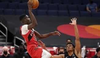 Toronto Raptors forward Chris Boucher (25) shoots over San Antonio Spurs forward Keldon Johnson (3) during the first half of an NBA basketball game Wednesday, April 14, 2021, in Tampa, Fla. (AP Photo/Chris O'Meara)