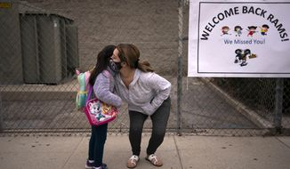 6-year-old Amanda Duran gets a hug from her mother, Lizette, on the first day of school at Heliotrope Elementary School in Maywood, Calif., Tuesday, April 13, 2021. More than a year after the pandemic forced all of California's schools to close classroom doors, some of the state's largest school districts are slowly beginning to reopen this week for in-person instruction.(AP Photo/Jae C. Hong)