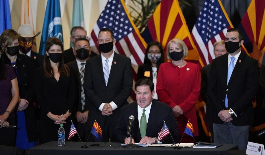 Surrounded by Arizona legislators, Republican Arizona Gov. Doug Ducey speaks at a bill signing allowing a major expansion of sports betting in Arizona at an event at the Heard Museum Thursday, April 15, 2021, in Phoenix. The measure approved by the Legislature adds additional types of table games at tribal casinos and for the first time allows sports betting under licenses issued to tribes and pro sports teams. (AP Photo/Ross D. Franklin)