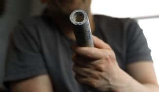 Troy Hernandez, an environmental justice activist with Pilsen Environmental Rights and Reform Organization shows a piece of lead pipe obtained from his residence during his home renovation, Friday, April 9, 2021 in Chicago's Pilsen neighborhood. Hernandez recently spent $15,000 to replace the lead service lines bringing water into his home. (AP Photo/Shafkat Anowar)