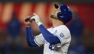 Kansas City Royals' Hunter Dozier celebrates at second base after hitting an RBI-double during the fourth inning of a baseball game against the Toronto Blue Jays, Thursday, April 15, 2021, in Kansas City, Mo. (AP Photo/Charlie Riedel)