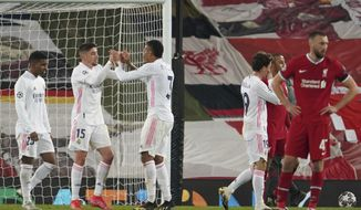 Real Madrid's Federico Valverde, left, and Real Madrid's Eder Militao celebrate celebrate at the end of the Champions League quarter final second leg soccer match between Liverpool and Real Madrid at Anfield stadium in Liverpool, England, Wednesday, April 14, 2021. (AP Photo/Jon Super)