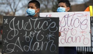 FILE - In this Tuesday, April 6, 2021, file photo, Jacob Perea, 7, left and Juan Perea, 9, hold signs as they attend a news conference following the death of 13-year-old Adam Toledo, who was shot by a Chicago Police officer at about 2 a.m. on March 29 in an alley. The independent board that reviews Chicago police shootings says it will release body camera footage and other investigation materials Thursday, April 15, 2021, pertaining to the fatal shooting. (AP Photo/Shafkat Anowar, File)