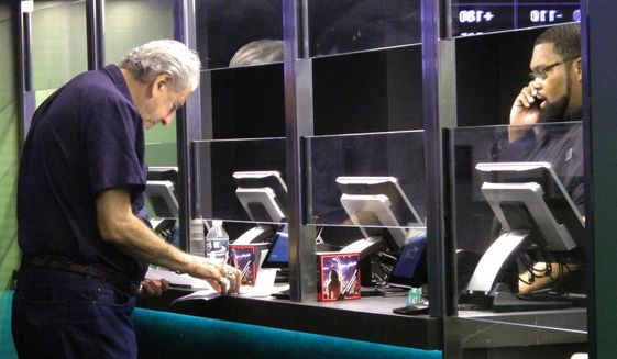 In this Oct. 8, 2019 photo, a customer makes a sports bet at the DraftKings sports book at Resorts Casino in Atlantic City, N.J. On Tuesday, March 30, 2021, DraftKings acquired the video production and distribution company Vegas Sports Information Network to add content to DraftKings' operations in 14 states. (AP Photo/Wayne Parry) **FILE**