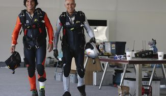 "FILE - In this May 12, 2015, file photo, former Swiss pilot Yves Rossy, known as a ""jetman,"" right, and his protege Vincent Reffet, prepare for a fly in Dubai, United Arab Emirates. Reffet, one of Dubai's famed ""jetman"" killed in a crash in November, failed to deploy the emergency parachute attached to the winged engines strapped to his back, an investigative report released Thursday, April 15, 2021 found. (AP Photo/Kamran Jebreili, File)"