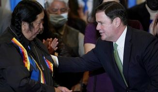 Arizona Republican Gov. Doug Ducey, right, talks with Dr. Damon R. Clarke, left, Chairman of the Hualapai Tribe, after a bill signing allowing a major expansion of sports betting in Arizona at an event at the Heard Museum Thursday, April 15, 2021, in Phoenix. The measure approved by the Legislature adds additional types of table games at tribal casinos and for the first time allows sports betting under licenses issued to tribes and pro sports teams. (AP Photo/Ross D. Franklin)