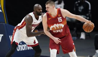 Denver Nuggets center Nikola Jokic is defended by Miami Heat center Dewayne Dedmon during the second half of an NBA basketball game Wednesday, April 14, 2021, in Denver. (AP Photo/David Zalubowski)
