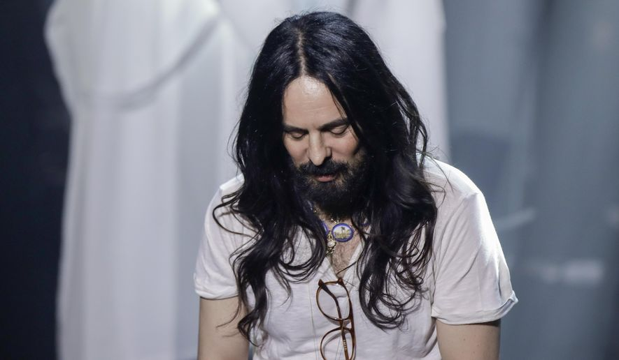 FILE - In this Wednesday, Feb. 19, 2020 file photo, Alessandro Michele acknowledges the applause of the audience at the end of Gucci's Fall/Winter 2020/2021 collection, presented in Milan, Italy. Gucci creative director Alessandro Michele is celebrating the fashion house's 100-year anniversary, giving historic sweep to a collection unveiled virtually Thursday that embraced its equestrian heritage, borrowed references from the Tom Ford-era and outright stole from a sister brand Balenciaga. (AP Photo/Luca Bruno, File)