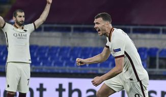 Roma's Edin Dzeko, right, celebrates after scoring his team's first goal during the Europa League second leg quarterfinal soccer match between Roma and Ajax at Rome's Olympic stadium, Italy, Thursday, April 15, 2021. (Luciano Rossi/LaPresse via AP)