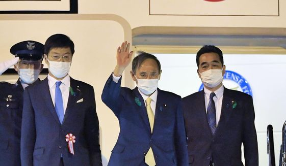 Japanese Prime Minister Yoshihide Suga, center, waves, on his departure for the U.S., at Haneda airport, in Tokyo Thursday, April 15, 2021. Suga headed to Washington on Thursday to become the first foreign leader to have a face-to-face meeting with President Joe Biden for talks that would reaffirm the strength of their alliance and how to deal with China's growing assertiveness and challenge to democratic values. (Kyodo News via AP)
