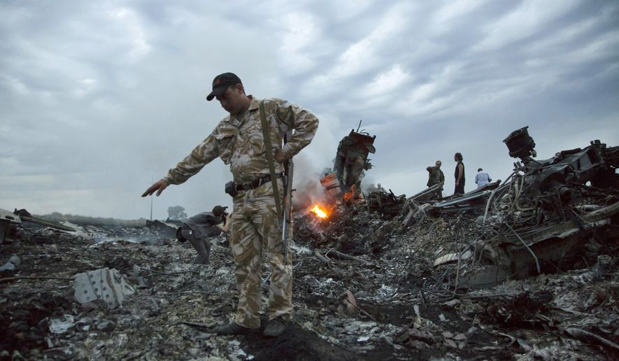 """FILE- In this July 17, 2014, file photo, people walk amongst the debris at the crash site of MH17 passenger plane near the village of Grabovo, Ukraine, that left 298 people killed. A lawyer for relatives of people killed in the 2014 downing of Malaysia Airlines Flight 17 over eastern Ukraine told a court hearing Thursday, April 15, 2021 that 290 family members and partners of the victims have filed compensation claims for """"emotional distress"""" against four suspects charged in the downing. (AP Photo/Dmitry Lovetsky, File)"""