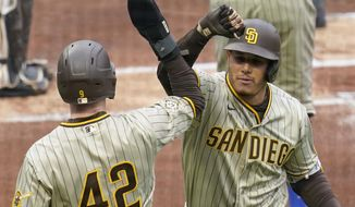 San Diego Padres' Manny Machado, right, is greeted by a teammate after hitting a two-run home run against the Pittsburgh Pirates during the first inning of a baseball game, Thursday, April 15, 2021, in Pittsburgh. (AP Photo/Keith Srakocic)