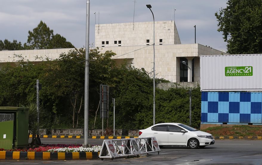 A car drives past the French Embassy, in Islamabad, Pakistan, Thursday, April 15, 2021. The French embassy in Pakistan on Thursday advised all of its nationals and companies to temporarily leave the country after anti-France violence erupted in the Islamic nation over the arrest of a radical leader. Saad Rizvi was arrested Monday for threatening the government with mass protests if it did not expel French envoy Marc Baréty over the publication depictions of Islam's Prophet Muhammad. (AP Photo/Anjum Naveed)