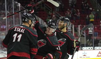 Carolina Hurricanes center Jordan Staal (11) and defenseman Jaccob Slavin, right, congratulate right wing Andrei Svechnikov (37) following Svechnikov's goal against the Nashville Predators during the second period of an NHL hockey game in Raleigh, N.C., Thursday, April 15, 2021. (AP Photo/Gerry Broome)