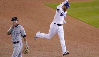 Los Angeles Dodgers' Justin Turner, right, rounds second after hitting a solo home run as Colorado Rockies second baseman Garrett Hampson looks on during the third inning of a baseball game Wednesday, April 14, 2021, in Los Angeles. (AP Photo/Mark J. Terrill)