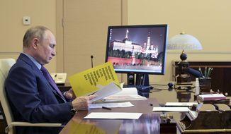 Russian President Vladimir Putin attends a meeting via video conference at the Novo-Ogaryovo residence outside Moscow, Russia, Thursday, April 15, 2021. (Alexei Druzhinin, Sputnik, Kremlin Pool Photo via AP)