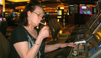 In this March 9, 2016 photo, Cheryl Palina of Philadelphia lights a cigarette while playing a slot machine at the Tropicana casino in Atlantic City, N.J.  On Thursday, April 15, 2021, health advocates, smoking opponents and some New Jersey lawmakers called for the state's temporary ban on casino smoking, imposed last year due to the coronavirus pandemic, be made permanent once the outbreak ends. (AP Photo/Wayne Parry)