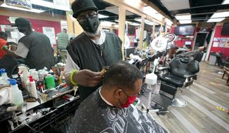 Wallace Wilson, top, cuts the hair of James McRae, Friday, April 9, 2021, in Hyattsville, Md. Wilson is a member of the Health Advocates In Reach & Research (HAIR) program, which helps barbers and hair stylists to get certified to talk to community members about health. During the COVID-19 pandemic, a team of certified barbers have been providing factual information to customers about vaccines, a topic that historically has not been trusted by members of black communities because of the health abuse the race has endured over the years. (AP Photo/Julio Cortez)