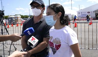 Azul Thurdekoos, 16, right, is interviewed with with her father Ricardo after getting the Pfizer COVID-19 vaccine at a FEMA vaccination center at Miami Dade College after getting the Pfizer, Monday, April 5, 2021, in Miami. Any adult in Florida is now eligible to receive the coronavirus vaccine. In addition, the state announced that teens ages 16 and 17 can also get the vaccine with parental permission. (AP Photo/Lynne Sladky)