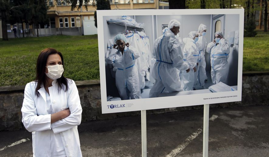 A Torlak Institute's employee waits for the visit of Serbian President Aleksandar Vucic in Belgrade, Serbia, Thursday, April 15, 2021. Serbia has announced it will begin packing and later producing Russia's Sputnik V coronavirus vaccine, which would make it the first European state outside Russia and Belarus to begin manufacturing the jab. (AP Photo/Darko Vojinovic)