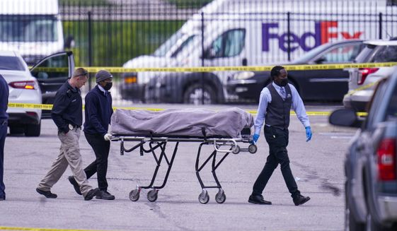 A body is taken from the scene where multiple people were shot at a FedEx Ground facility in Indianapolis, Friday, April 16, 2021. A gunman killed eight people and wounded several others before apparently taking his own life in a late-night attack at a FedEx facility near the Indianapolis airport, police said, in the latest in a spate of mass shootings in the United States after a relative lull during the pandemic. (AP Photo/Michael Conroy)