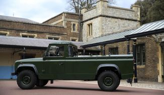 "The Jaguar Land Rover that will be used to transport the coffin of the Duke of Edinburgh at his funeral on Saturday, is pictured at Windsor Castle, in Berkshire, England, Wednesday, April 14, 2021. The modified Land Rover Defender TD5 130 chassis cab vehicle was made at Land Rover's factory in Solihull in 2003 and Philip oversaw the modifications throughout the intervening years, requesting a repaint in military green and designing the open top rear and special ""stops"" to secure his coffin in place. (Steve Parsons/Pool Photo via AP)"