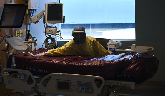 An essential worker thoroughly cleans a COVID-19 patient's room after they were transferred out of the intensive care unit at the Humber River Hospital in Toronto on Tuesday, April 13, 2021. (Nathan Denette/The Canadian Press via AP)