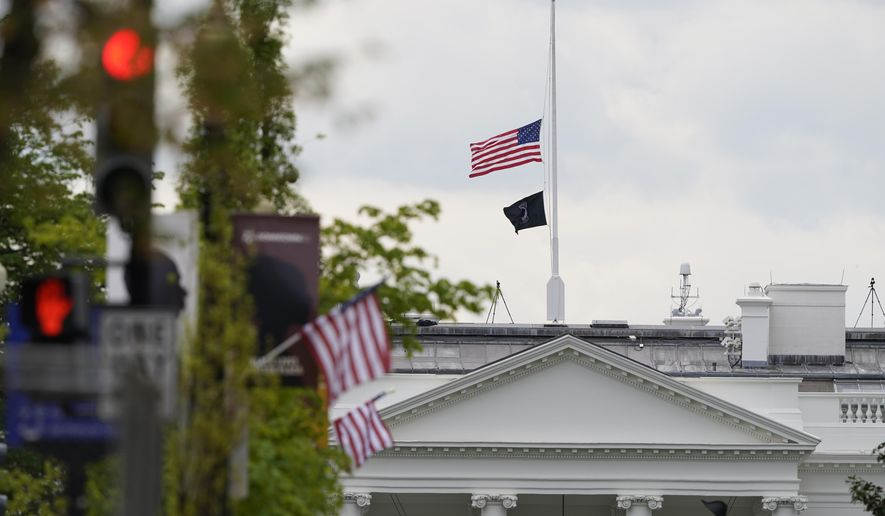 The American flag flies at half-staff over the White House in Washington, Friday, April 16, 2021. (AP Photo/Susan Walsh)