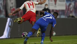 Hoffenheim's Ryan Sessegnon, right, challenges for the ball with Leipzig's Tyler Adams during the German Bundesliga soccer match between RB Leipzig and TSG 1899 Hoffenheim in Leipzig, Germany, Friday, April 16, 2021. (AP Photo/Michael Sohn, Pool)