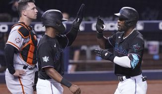 Miami Marlins' Magneuris Sierra, center, congratulates Starling Marte (6) after Marte hit a three-run home run in the eighth inning of a baseball game against the San Francisco Giants, Friday, April 16, 2021, in Miami. To the left is Giants catcher Buster Posey. (AP Photo/Marta Lavandier)