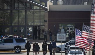 A group of people walk into Independence Community High School for funeral services for Iowa State Patrol Sgt. Jim Smith on Friday, April 16, 2021 in Independence, Iowa.  Smith, who was killed while trying to arrest a man barricaded in his Grundy Center home.(Kelsey Kremer /The Des Moines Register via AP)