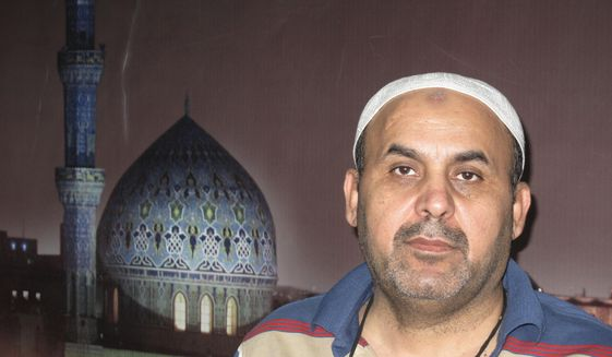 This 2003 photo shows Khodeir Majid at the AP office at the Palestine hotel.  Majid, who covered Iraq's numerous conflicts as a video producer and cameraman for the Associated Press over 17 years has died at the age of 64. Relatives said the cause of his death on Friday morning was complications due to the coronavirus.  (AP Photo/Ahmad Sami