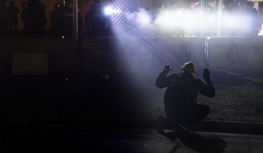 Police shine lights on a demonstrator with raised hands during a protest outside the Brooklyn Center Police Department on Wednesday, April 14, 2021, in Brooklyn Center, Minn., over Sunday's fatal shooting of Daunte Wright, a Black man, by a white police officer during a traffic stop. Wright's death came as the broader Minneapolis area awaits the outcome of the trial for Derek Chauvin, one of four officers charged in George Floyd's death in May 2020.(AP Photo/John Minchillo)