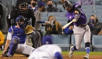 Colorado Rockies' Garrett Hampson, right, hits a home run during the third inning of a baseball game against the Los Angeles Dodgers Thursday, April 15, 2021, in Los Angeles. (AP Photo/Ashley Landis)