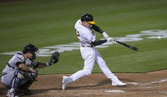 Oakland Athletics' Matt Chapman hits a two-run double in front of Detroit Tigers catcher Wilson Ramos during the sixth inning of a baseball game in Oakland, Calif., Thursday, April 15, 2021. (AP Photo/Jeff Chiu)
