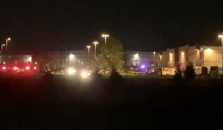 This image made from video shows a wide view of a building with flashing lights from emergency vehicles in Indianapolis, Friday, April 16, 2021. Police in Indianapolis say multiple people were shot and killed in a shooting late Thursday at a FedEx facility. (WRTV via AP)