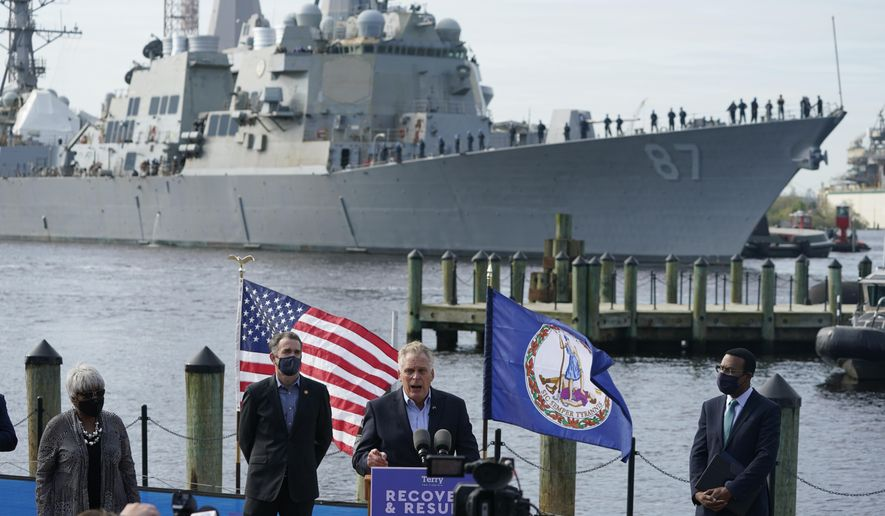 The USS Mason, an Arleigh Burke-class destroyer, glides past a news conference as former Gov. and Democratic gubernatorial candidate, Terry McAuliffe, at podium speaks, at Waterside in Norfolk, Va., Thursday, April 8, 2021. Virginia Gov. Ralph Northam, second from left, endorsed McAuliffe for governor. (AP Photo/Steve Helber)