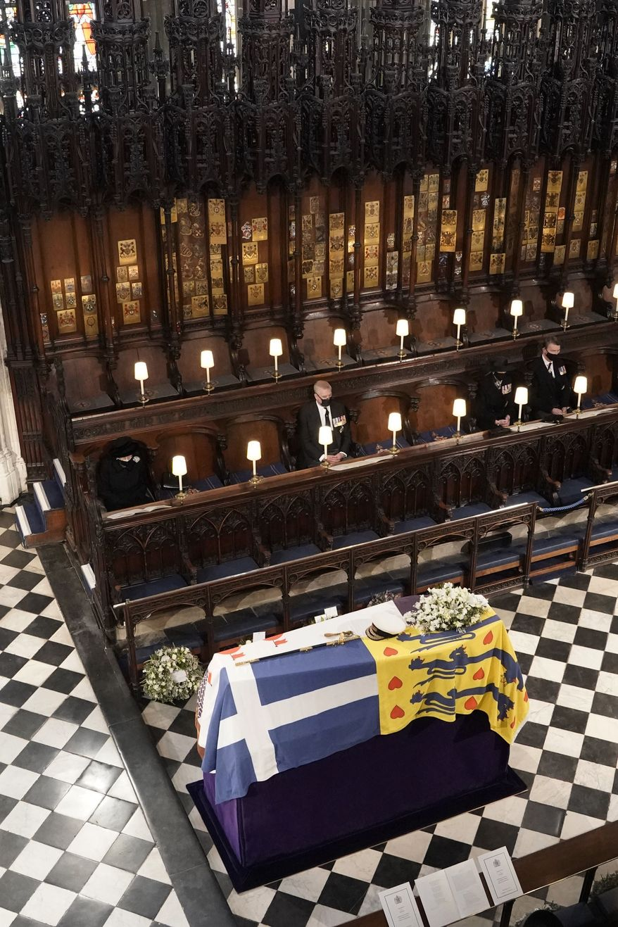 Britain's Queen Elizabeth II, left, Prince Andrew, Princess Anne the Princess Royal and Vice Admiral Timothy Laurence, right, look on the flag draped coffin in St. George's Chapel during the funeral of Prince Philip, the man who had been by the Queen's side for 73 years, at Windsor Castle, Windsor, England, Saturday April 17, 2021. Prince Philip died April 9 at the age of 99 after 73 years of marriage to Britain's Queen Elizabeth II. (Jonathan Brady/Pool via AP)