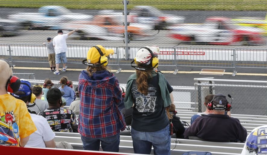 Fans watch the trucks pass on the front stretch during the NASCAR Truck Series auto race Saturday, April 17, 2021, at Richmond Raceway in Richmond, Va. (James H Wallace/Richmond Times-Dispatch via AP)