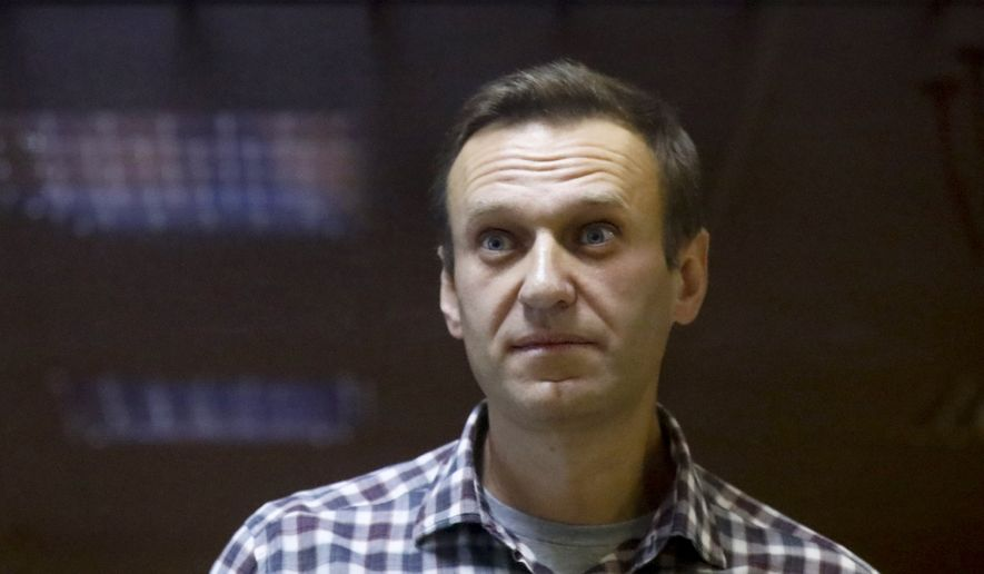 In this Saturday, Feb. 20, 2021, file photo, Russian opposition leader Alexei Navalny stands in a cage in the Babuskinsky District Court in Moscow, Russia. A doctor for the imprisoned Russian opposition leader, who is in the third week of a hunger strike, said on Saturday April 17, 2021, that his health is deteriorating rapidly and the 44-year-old Kremlin critic could be on the verge of death. (AP Photo/Alexander Zemlianichenko, File)