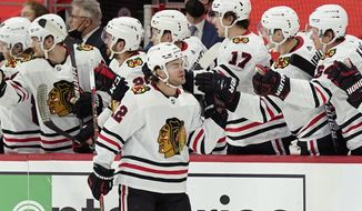 Chicago Blackhawks left wing Alex DeBrincat greets teammates after scoring during the second period of an NHL hockey game against the Detroit Red Wings, Saturday, April 17, 2021, in Detroit. (AP Photo/Carlos Osorio)