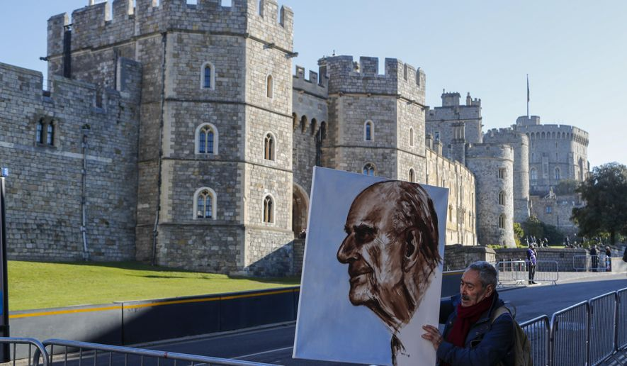 Artist Kaya Mar holds a portrait of Prince Philip ahead of the Prince's funeral in Windsor, England Saturday April 17, 2021. Philip died April 9 at the age of 99 after 73 years of marriage to Britain's Queen Elizabeth II. Coronavirus restrictions mean there will be only 30 mourners for the service, including the widowed queen, her four children and her eight grandchildren. (AP Photo/Frank Augstein)